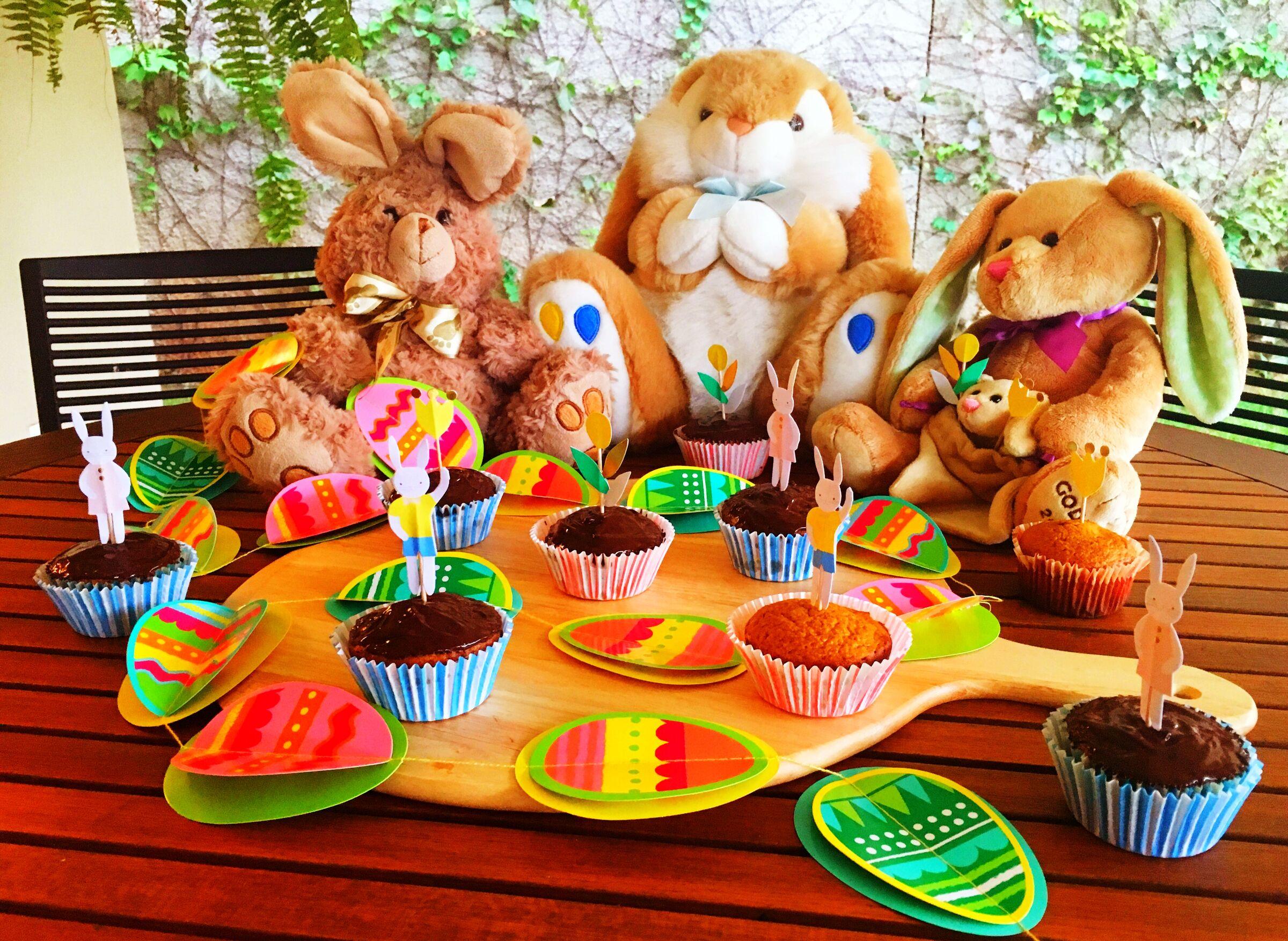 Coelhos de pelúcia ao redor de cupcakes