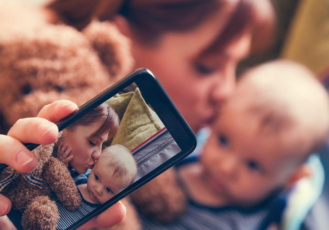 Mãe tirando foto com bebê