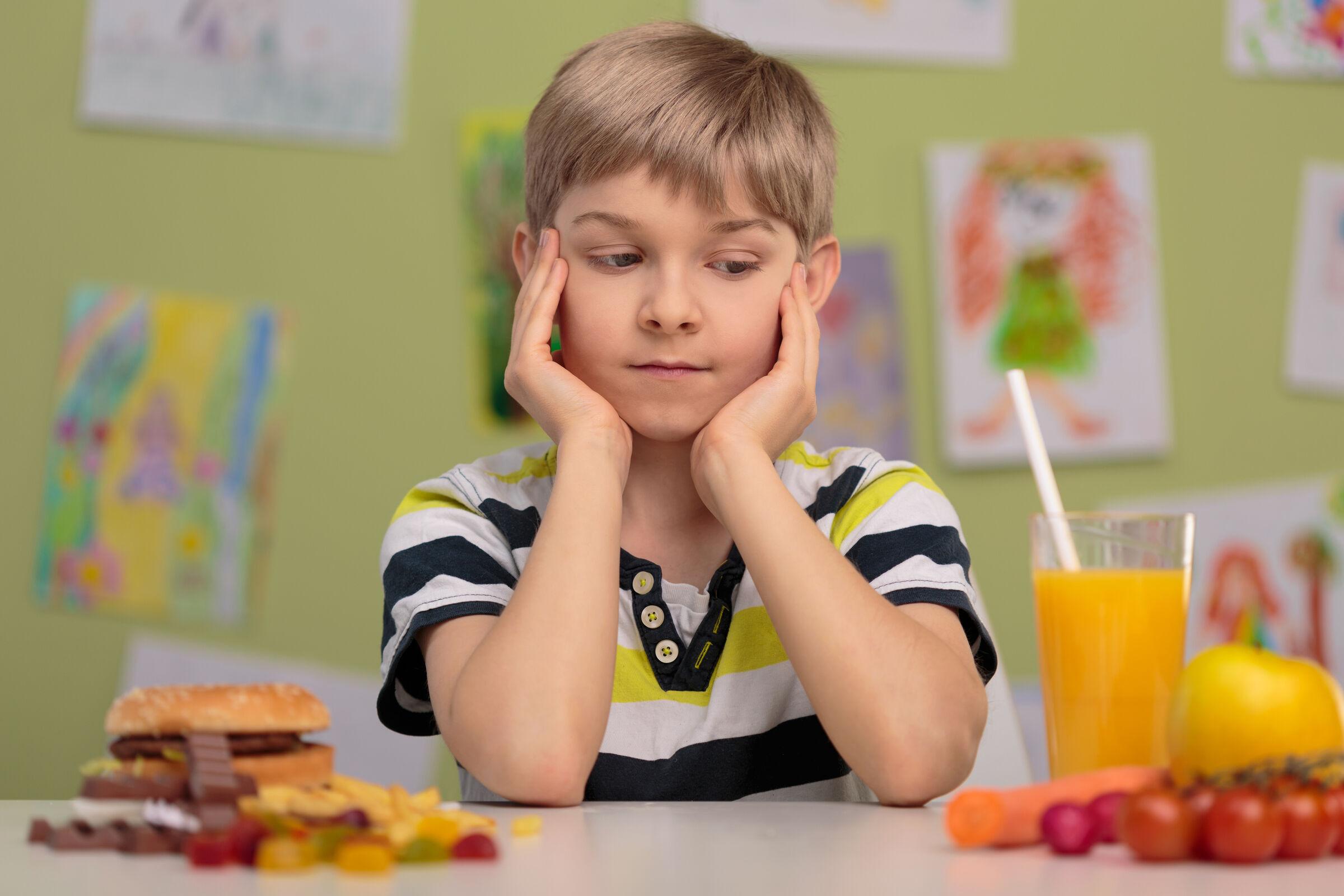 Criança indecisa entre guloseimas e comida saudável