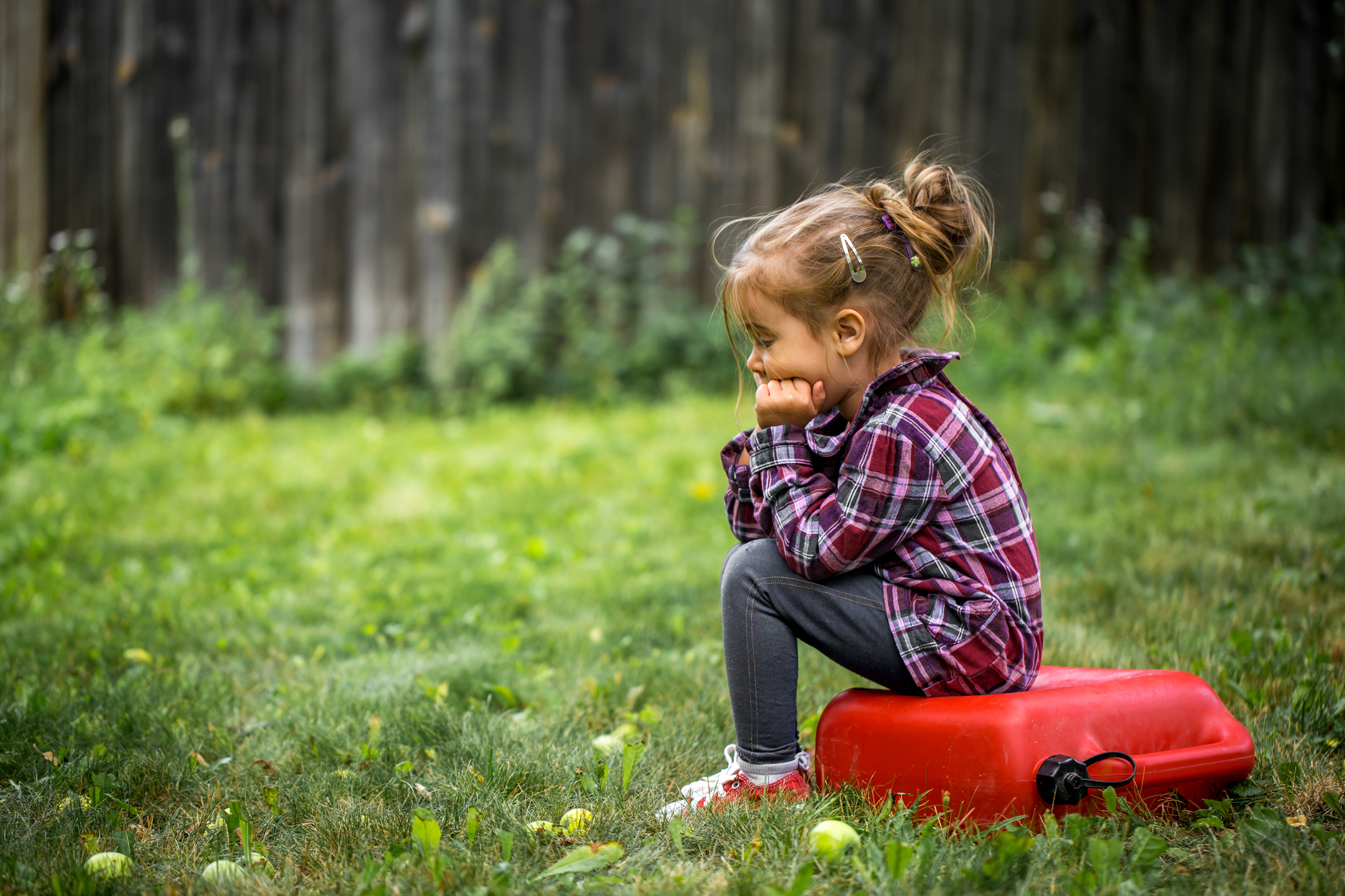 menina sentada triste
