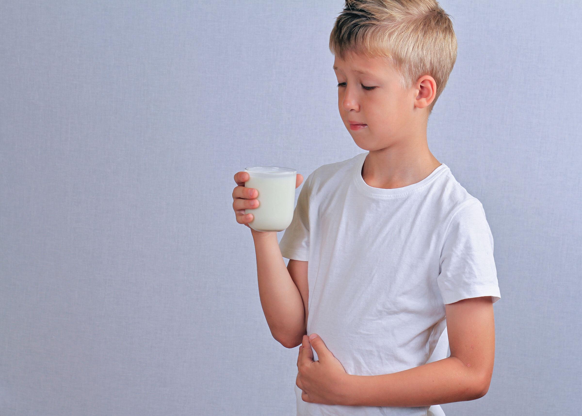 Criança com a mão na barriga e copo de leite da mão