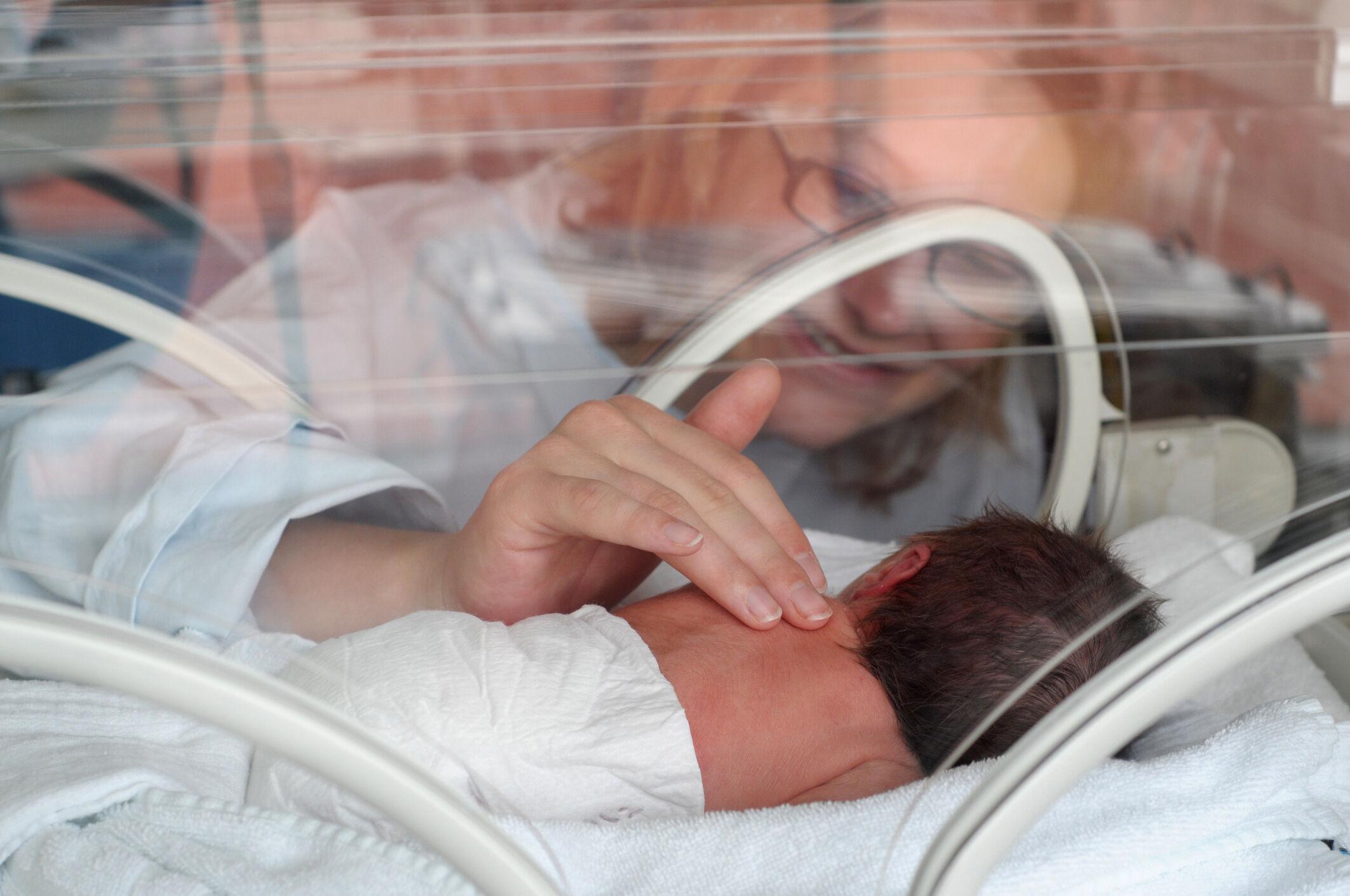 Mãe faz carinho em filho prematuro na incubadora