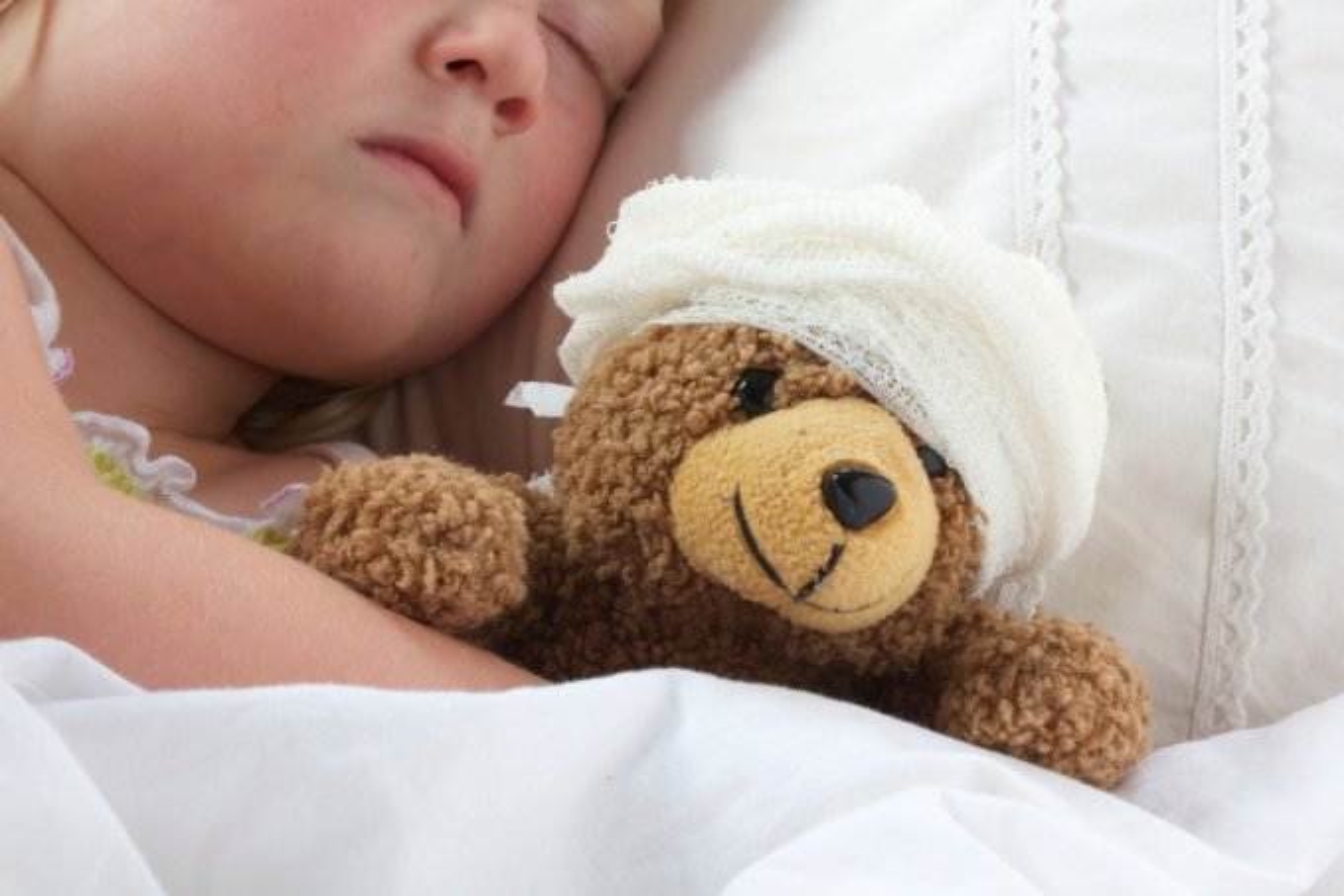 Bebê dormindo abraçado com urso em hospital