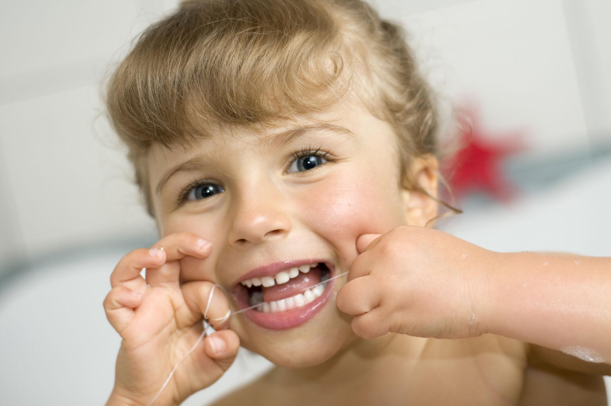 menina passando fio dental