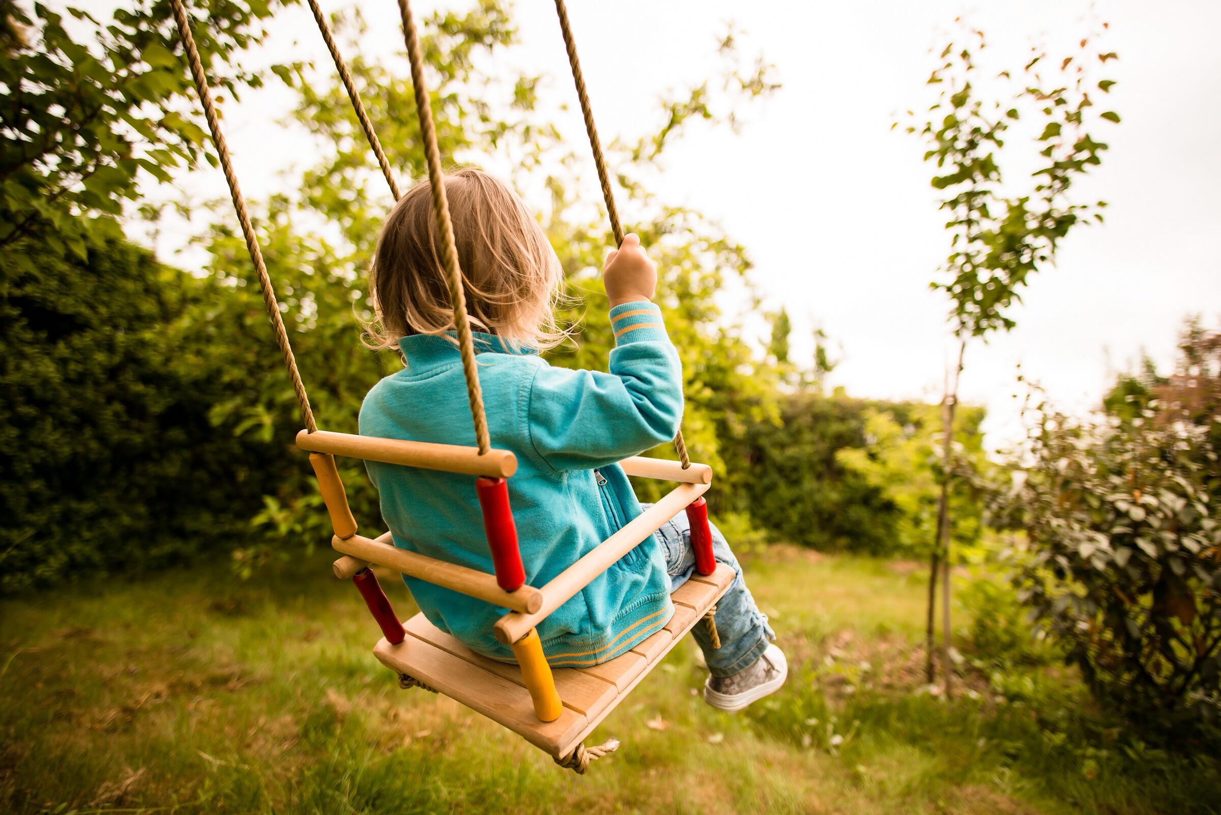 Criança sentada no balanço