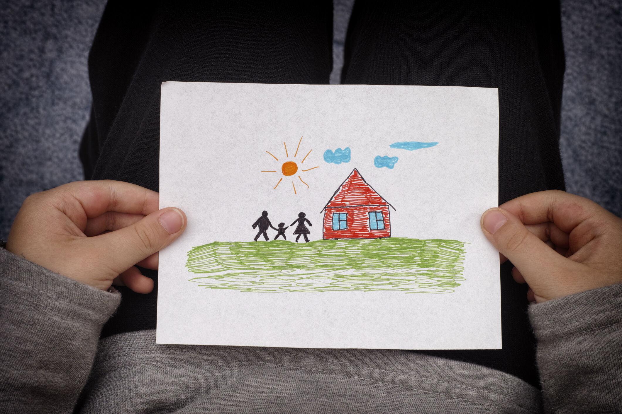 Crianças segura desenho de casa e família