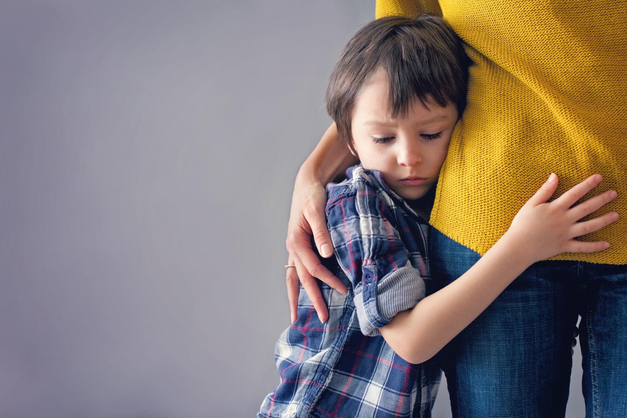 Criança abraçada com a mãe