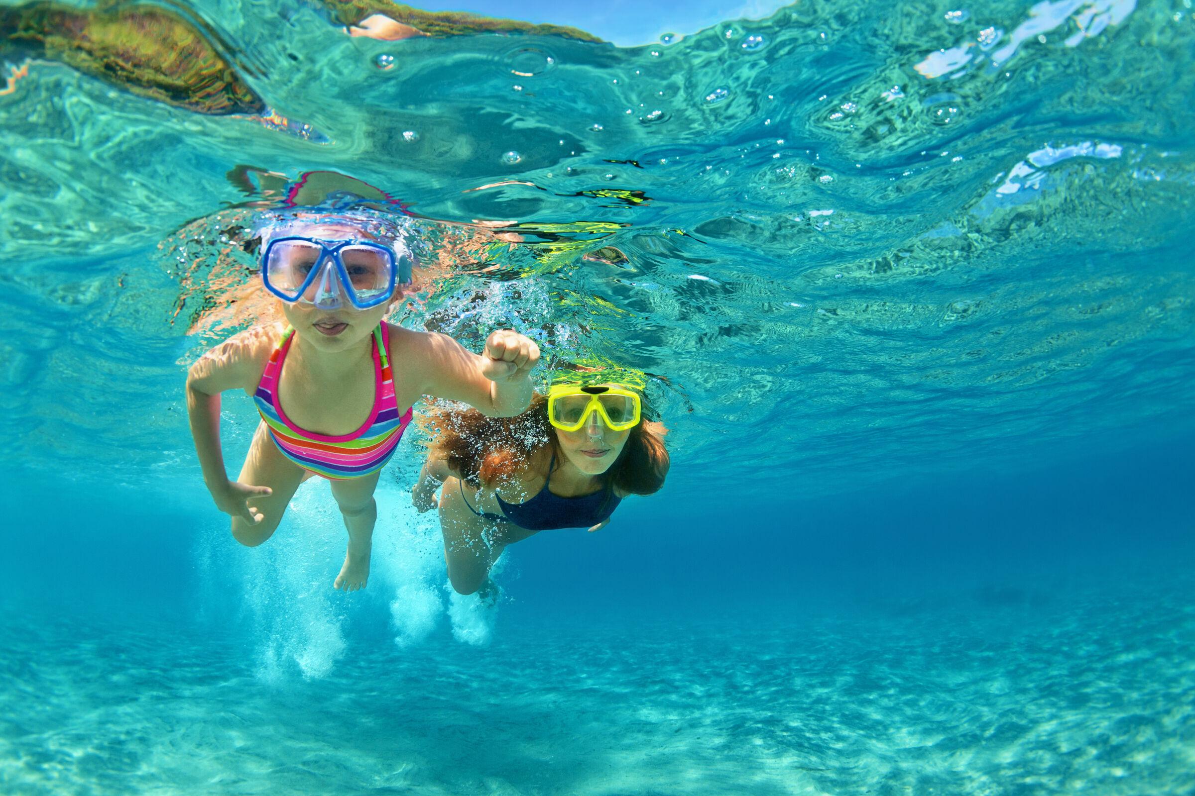 Mãe e filha fazendo mergulho nas férias