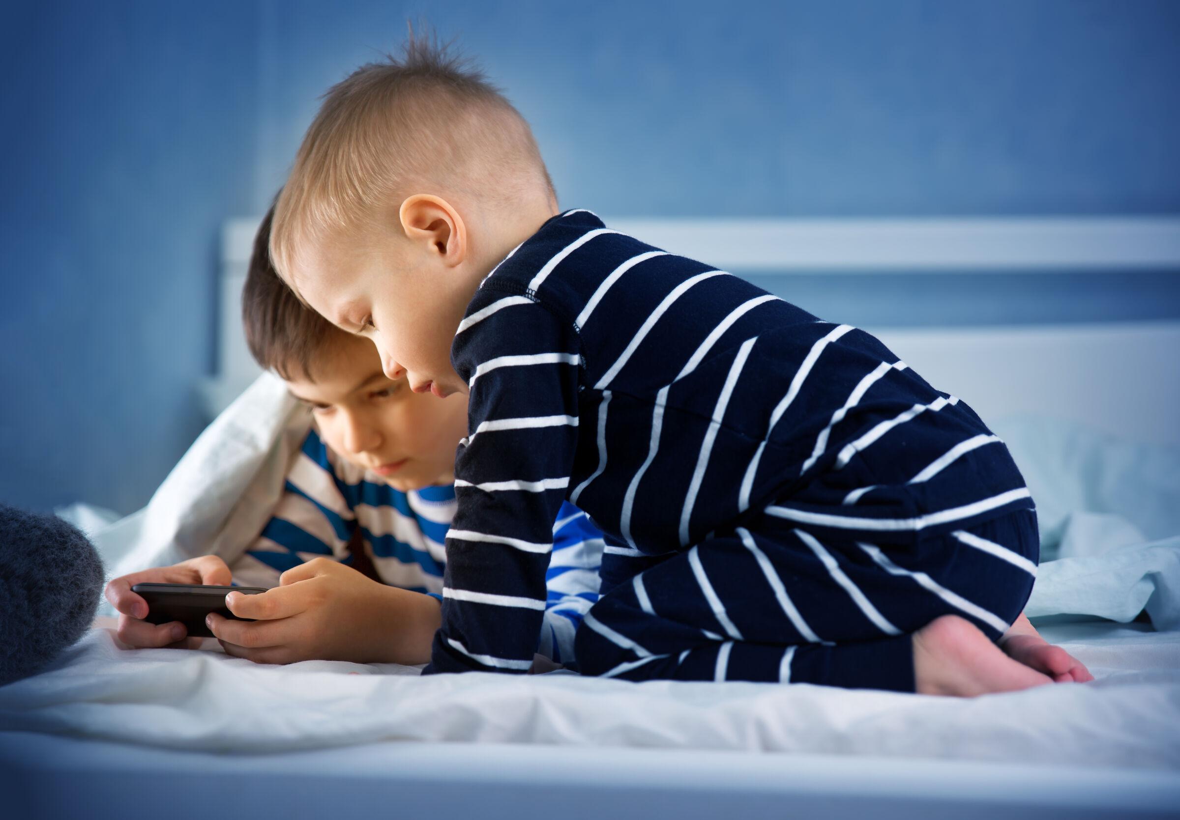 Duas crianças na cama olhando um celular