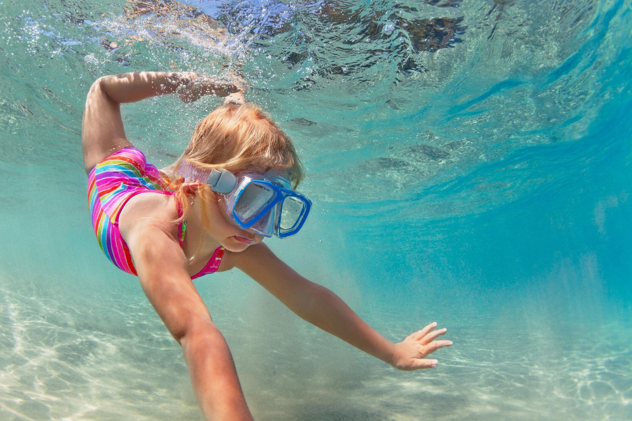 Criança mergulhando na piscina
