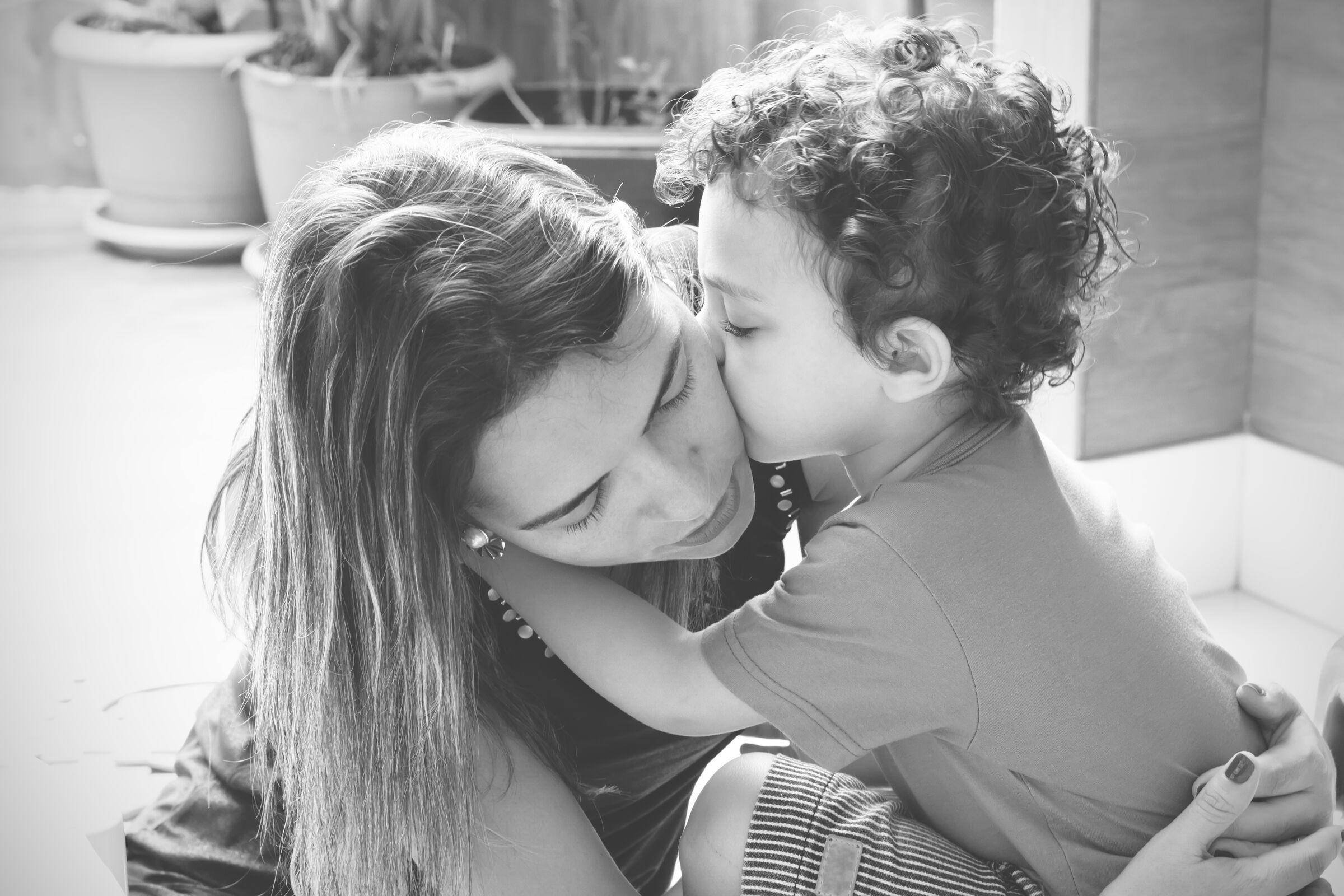 Criança de 2 anos dando beijo na mãe