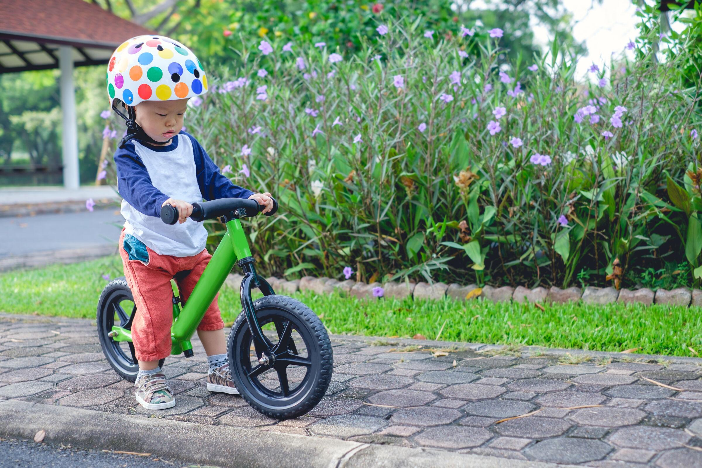 Criança andando de bicicleta usando capacete