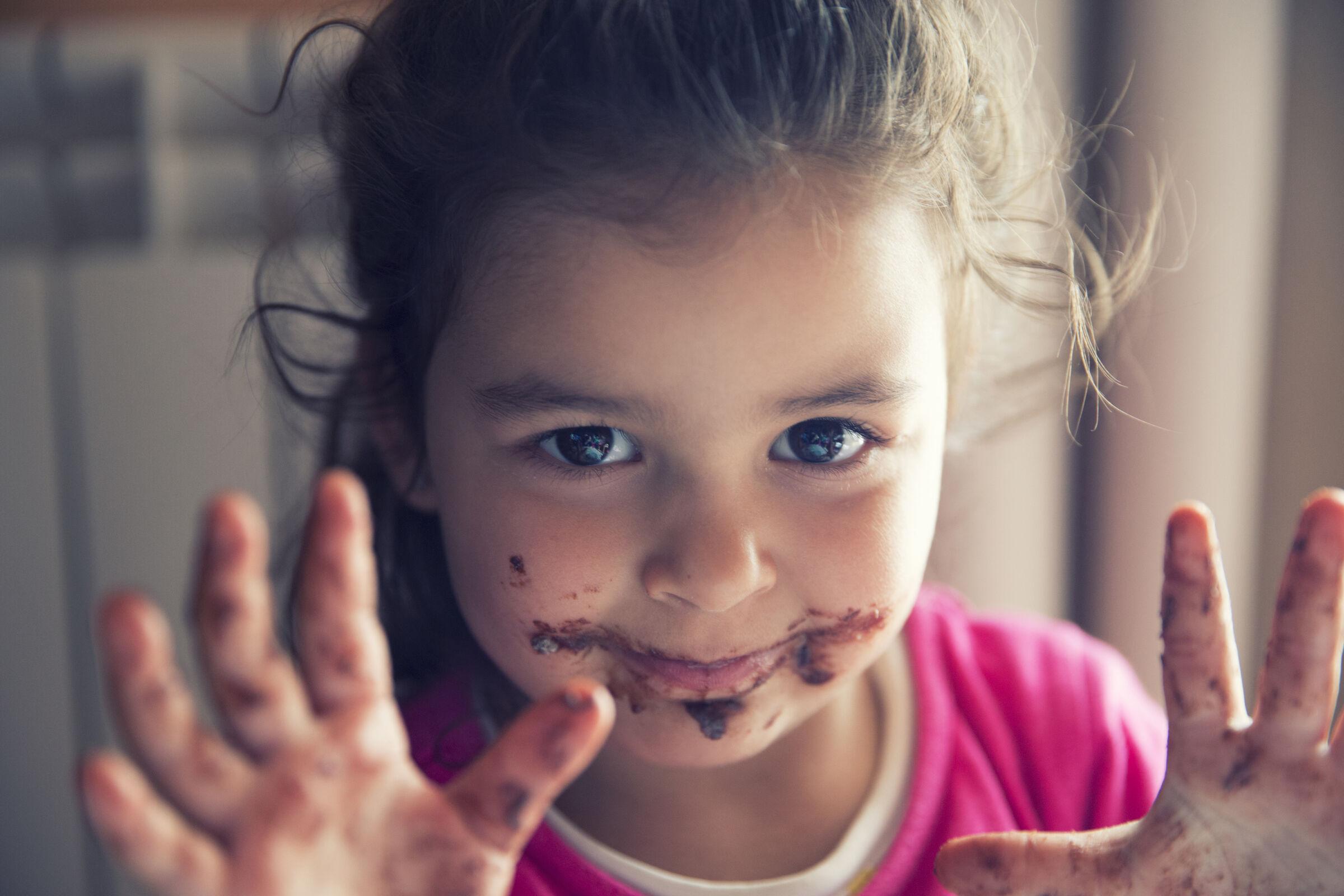 Menina com a boca e mãos sujas de chocolate