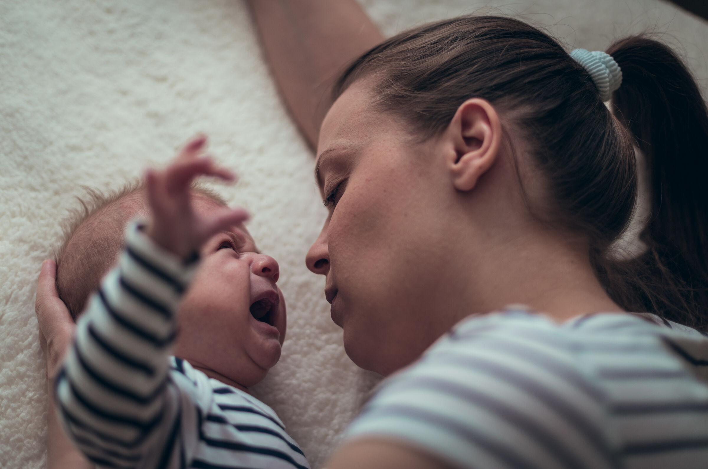 Mãe tentando acalmar bebê chorando - bebê high need