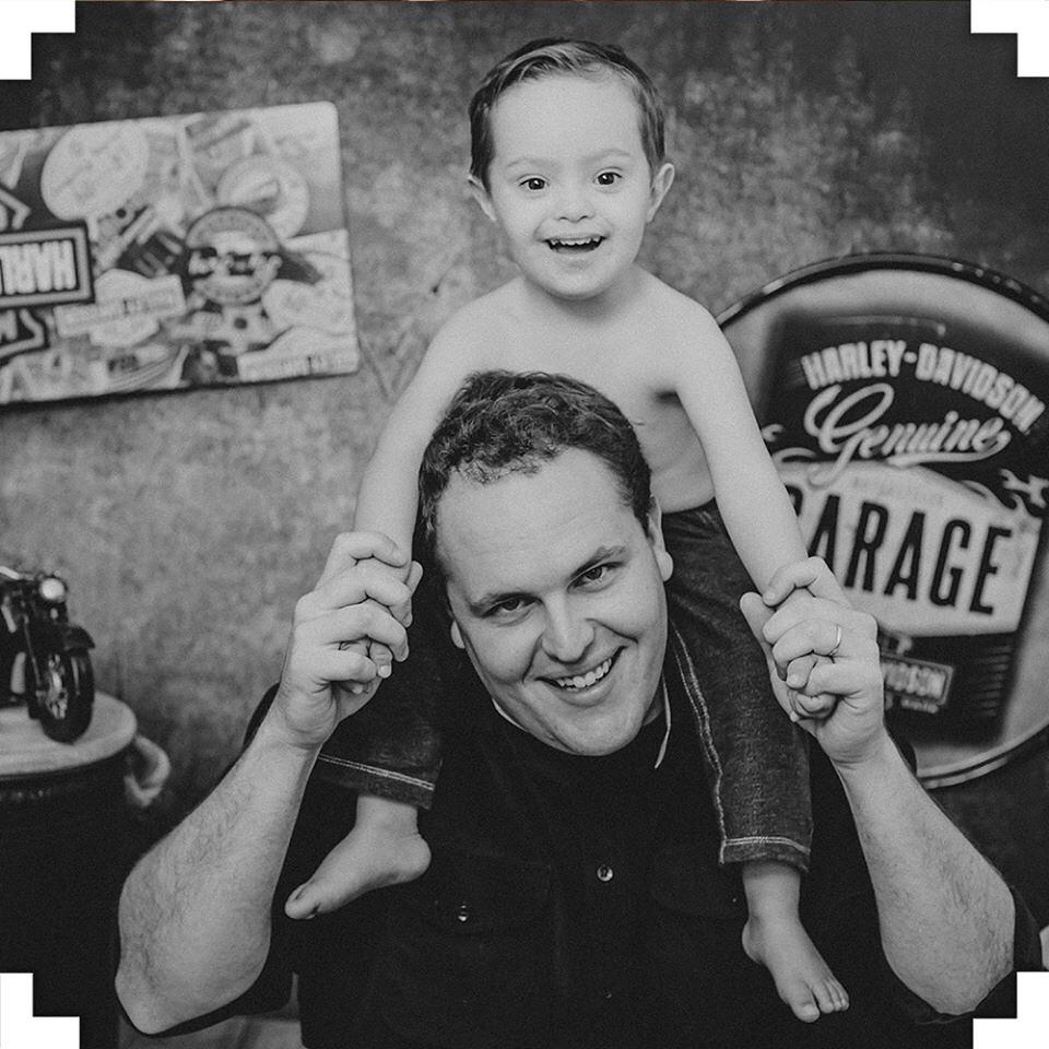 Menino sem blusa sentado no pescoço do pai, posando para uma foto