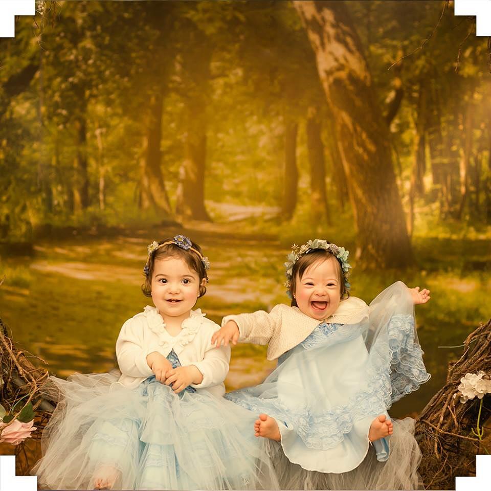Duas meninas, de vestido azul, sentadas posando para uma foto