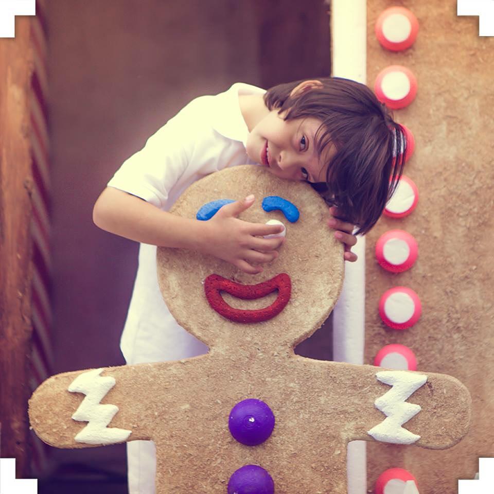 Garoto abraçando um boneco de biscoito gigante em um ensaio fotográfico