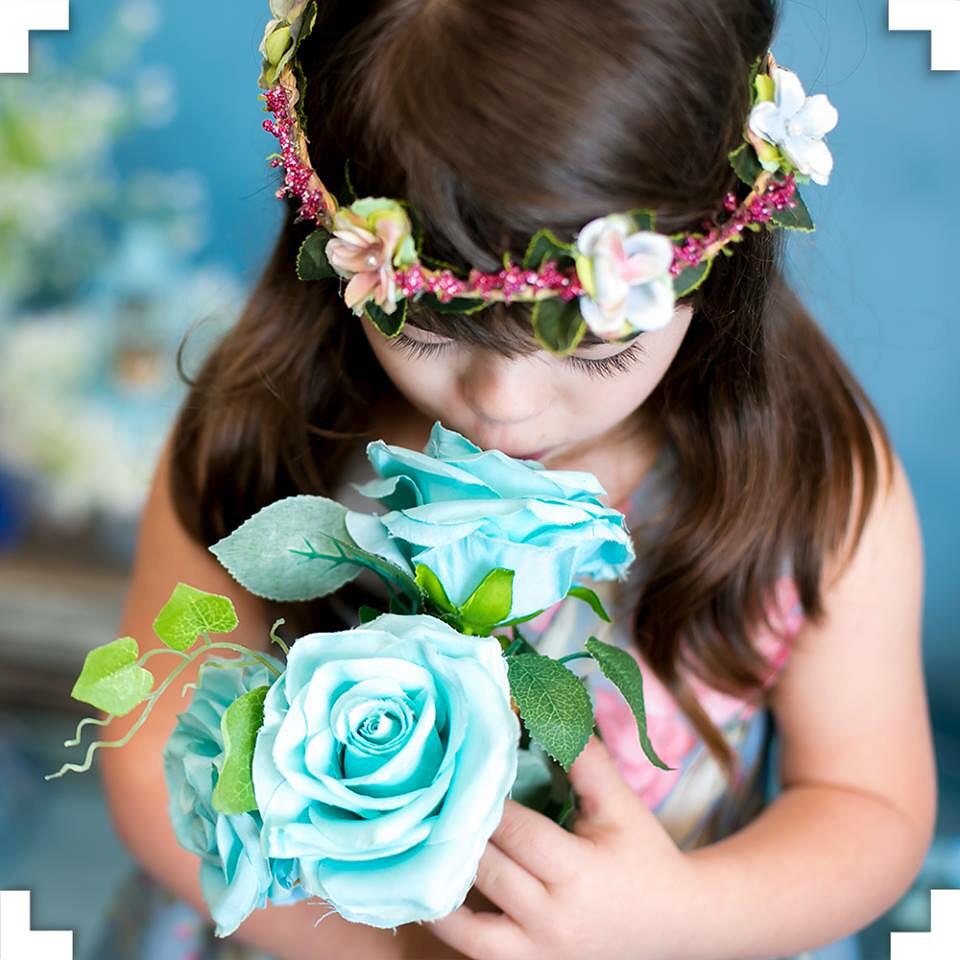 Garota cheirando uma flor azul em um ensaio fotográfico