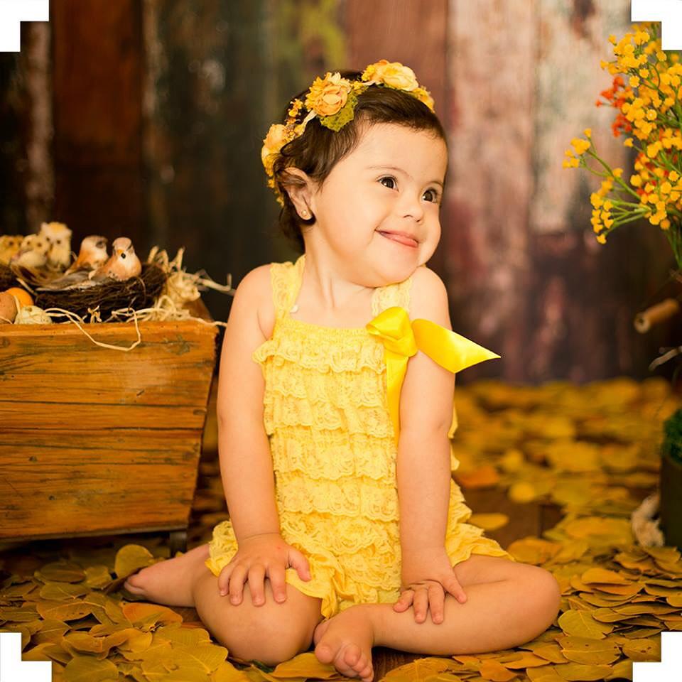 Garota de vestido amarelo e coroa de flores sentada no chão, sorrindo para a foto