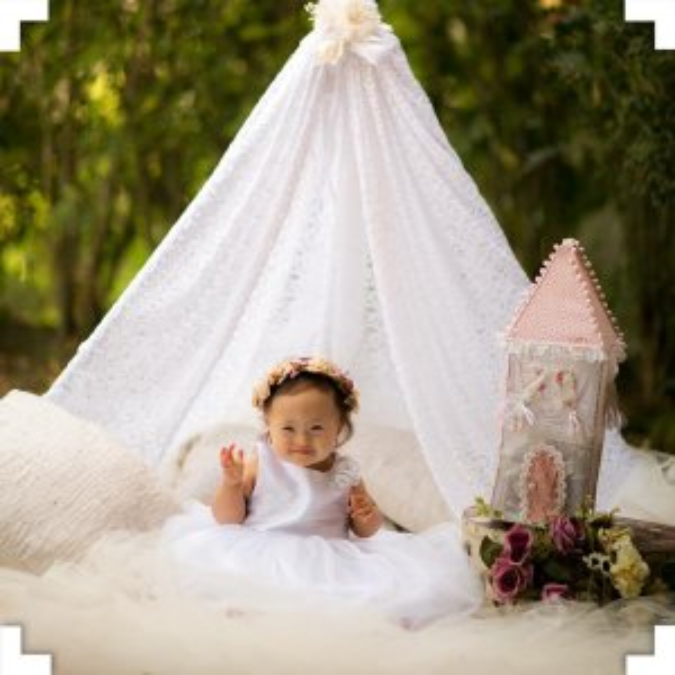 Recém-nascido de vestido branco, sentada em baixo de uma tenda branca em um ensaio fotográfico