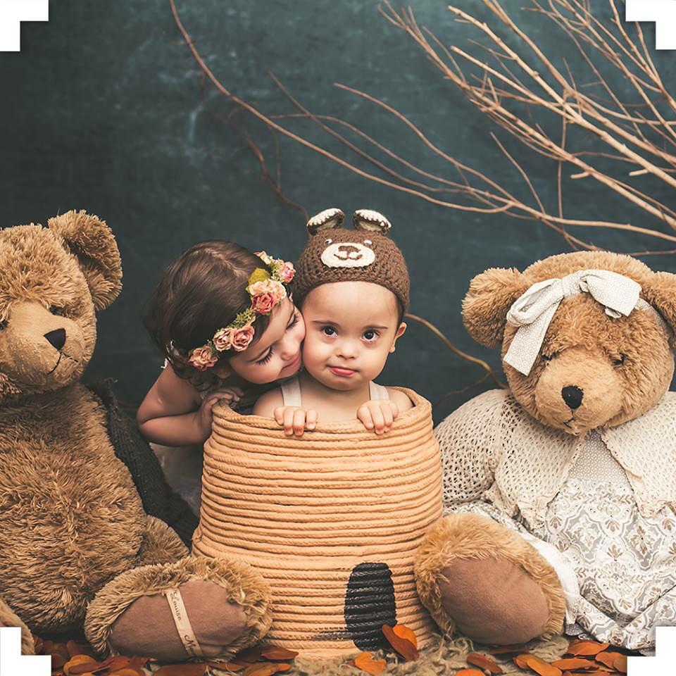 Dois bebês sentados em um cenário cenográfico posando para fotos
