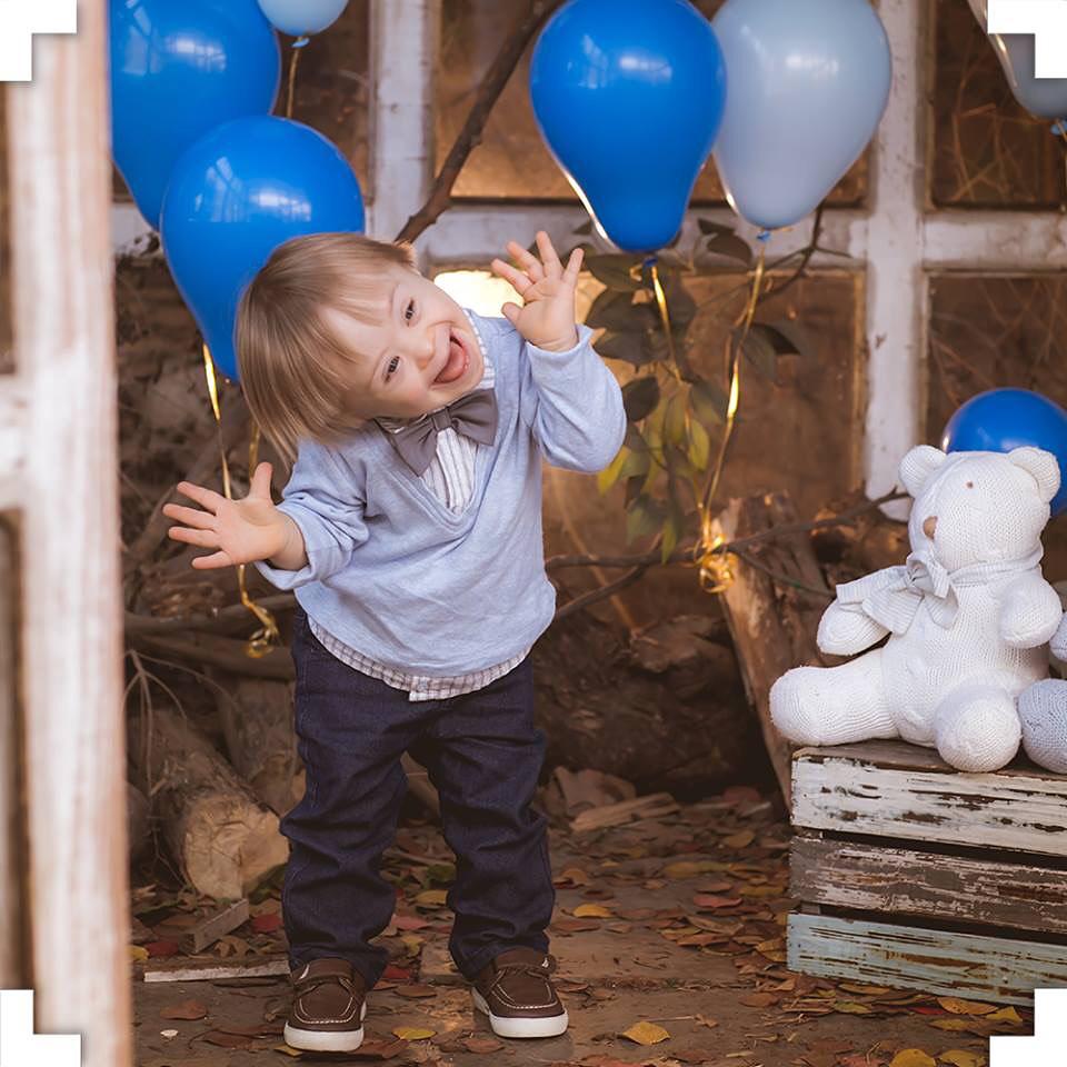 Bebê de camisa social e calça social, fazendo careta na frente da câmera, brincando