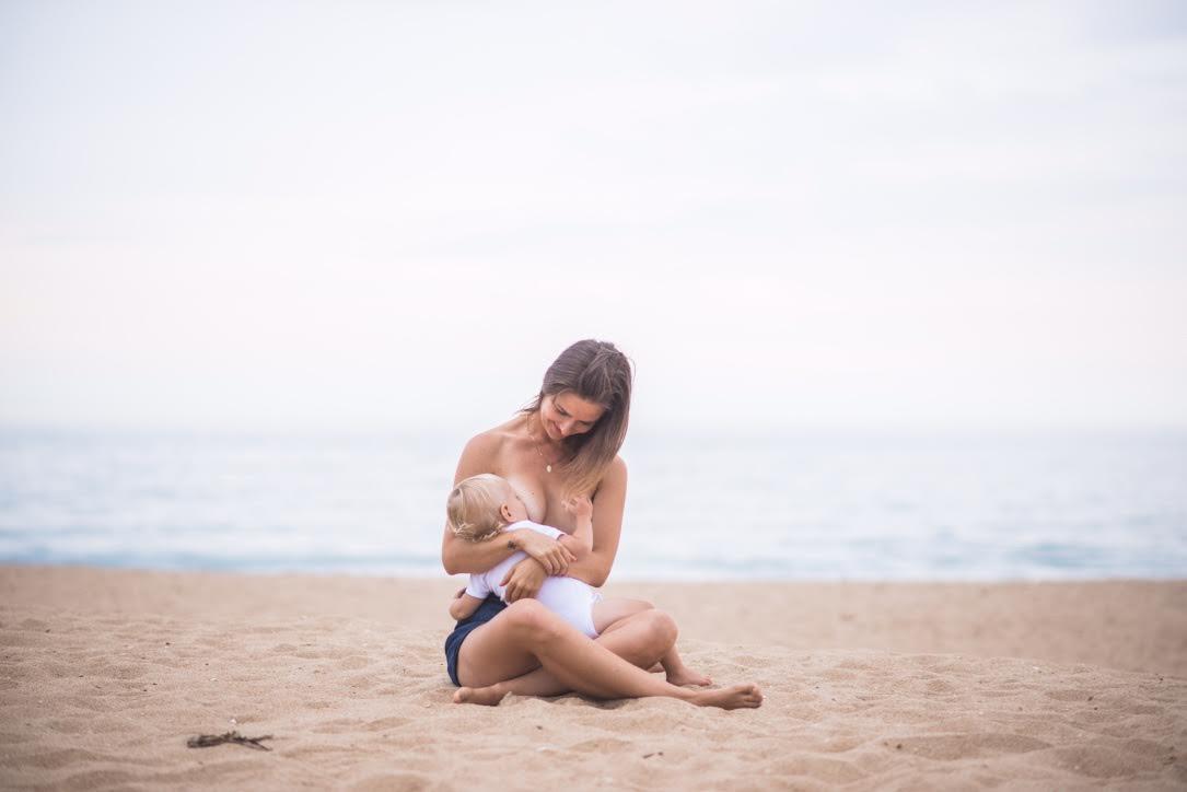 Mãe amamentando o filho na praia