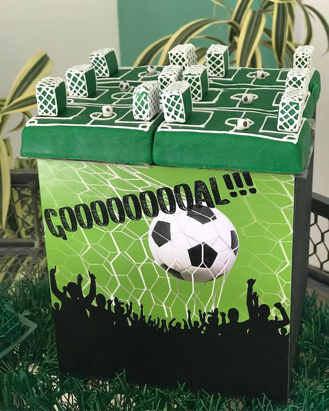 Bolo em formato de caixa, em que o topo lembra um jogo de tabuleiro de futebol, inspirado em Copa do Mundo