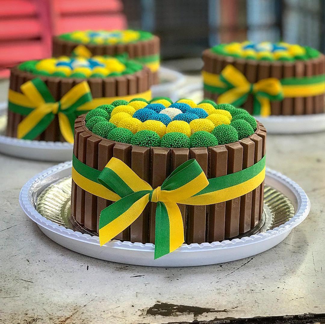 Bolo de chocolate com brigadeiros em cima enrolados com granulados verde e amarelo