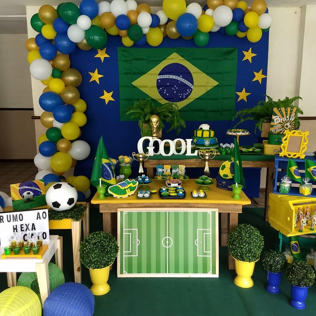Decoração baseada em Copa do Mundo, com balões verde e amarelo, bolo em formato de bola
