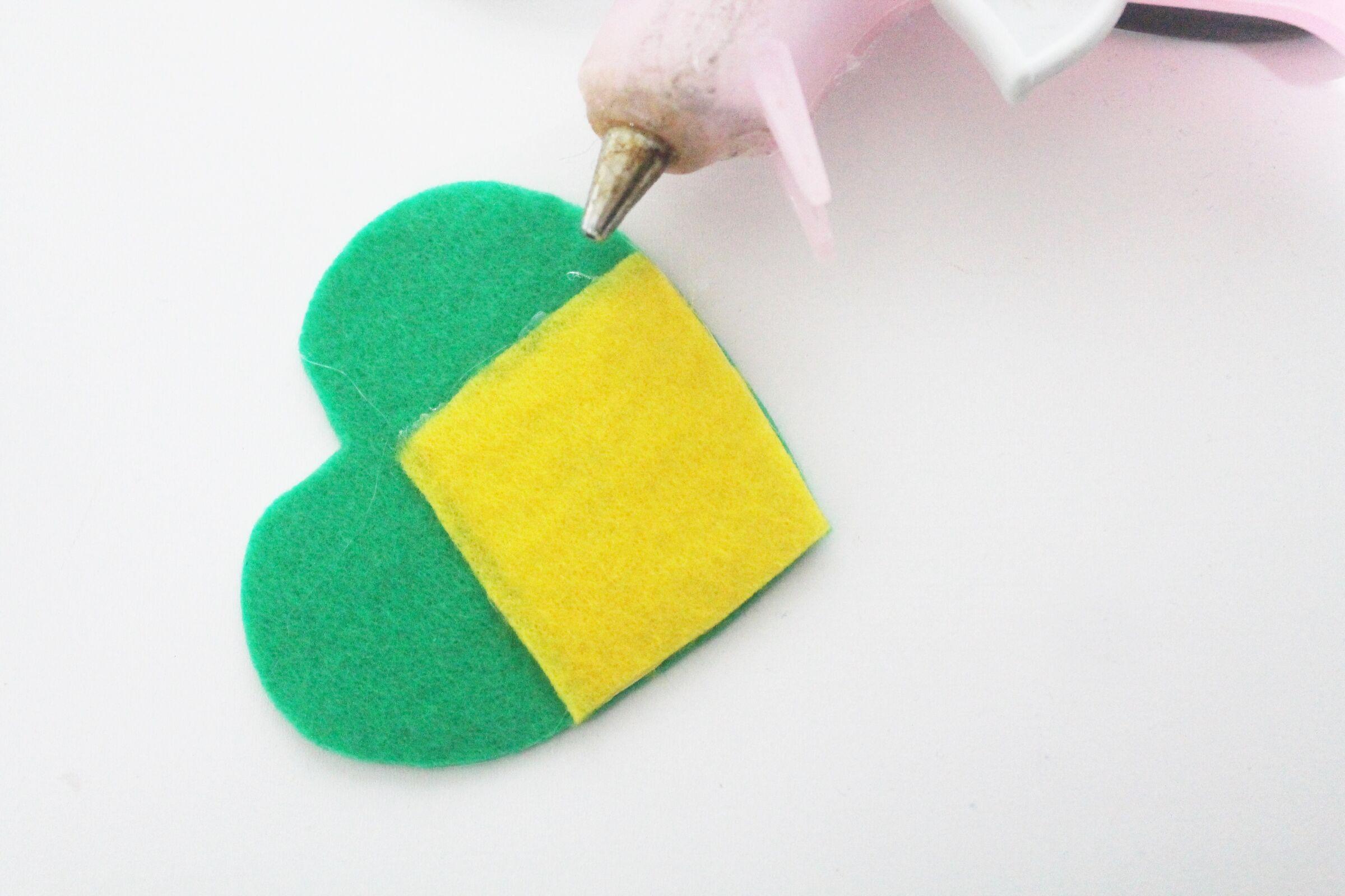 Recorte os excessos do feltro amarelo para que ele fique com o formato do feltro verde.