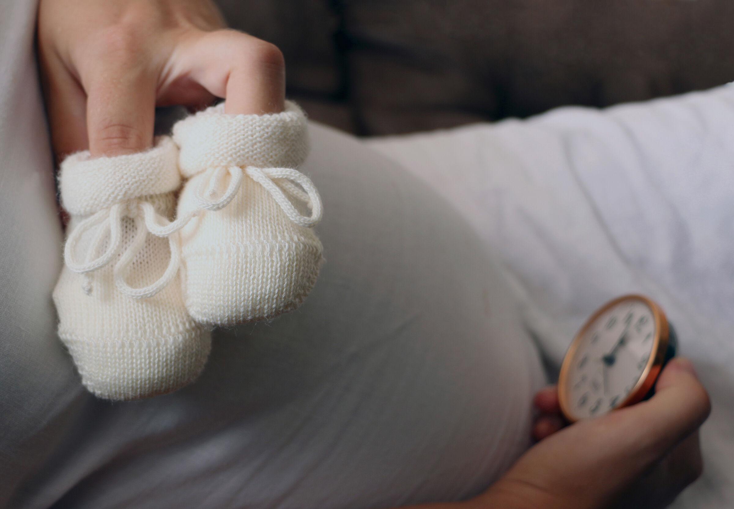 Grávida segura sapatinho de bebê no colo