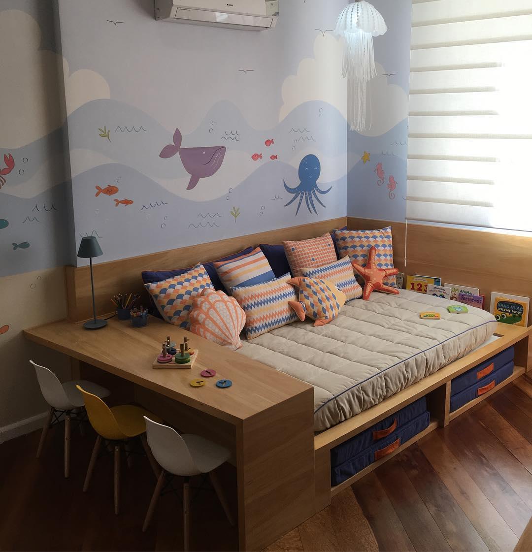 Quarto infantil com temática de fundo do mar, com uma cama embutida com escrivaninha de madeira