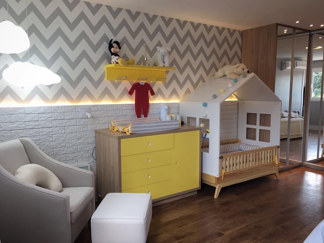 Quarto infantil com detalhes especialmente em amarelo, com cômoda e berço