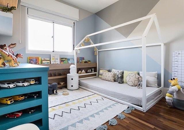 Quarto infantil decorado com uma cama montessori branca e tapete branco, com cômoda azul
