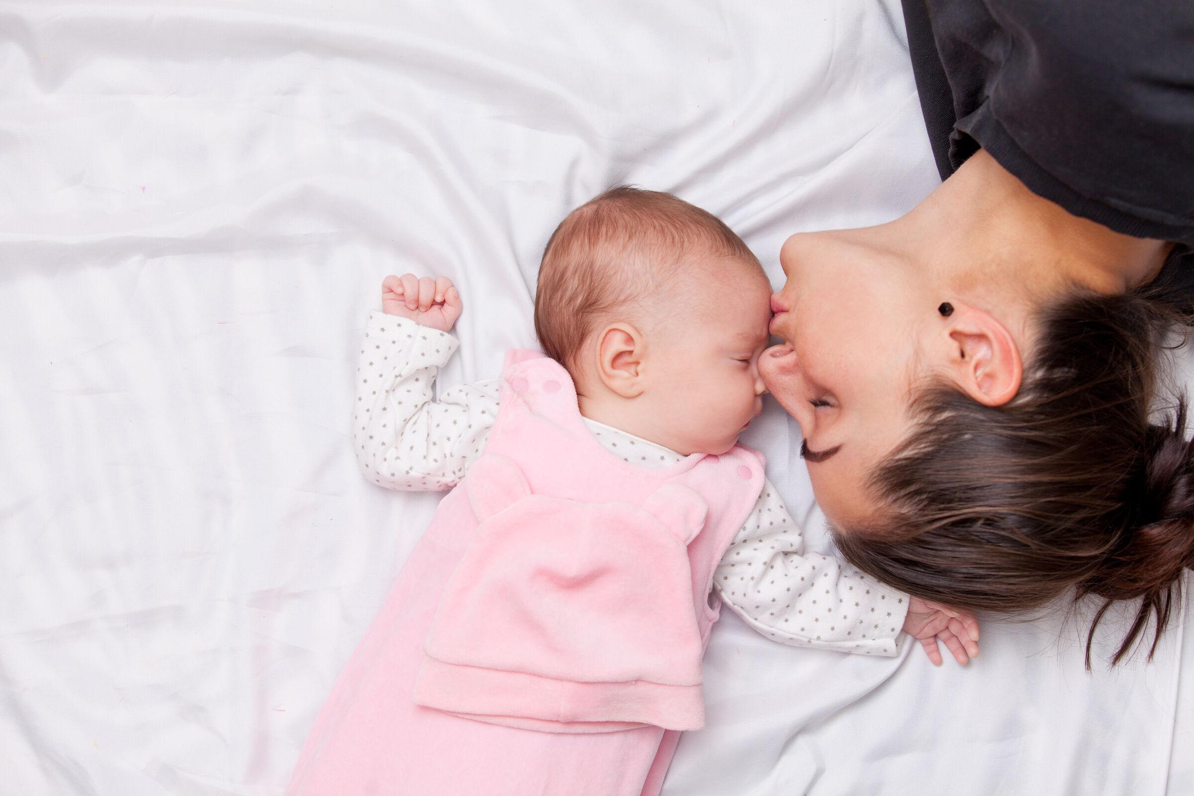 Mãe dando um beijinho na testa da filha que está dormindo de barriga para cima