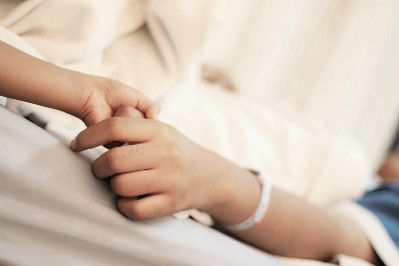 Criança segurando mão de adulto