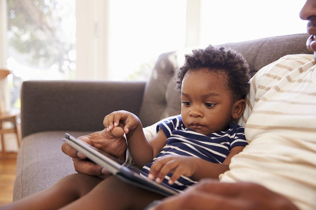 Criança usando o tablet com o pai