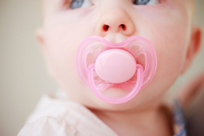 Close up of baby with pink pacifier