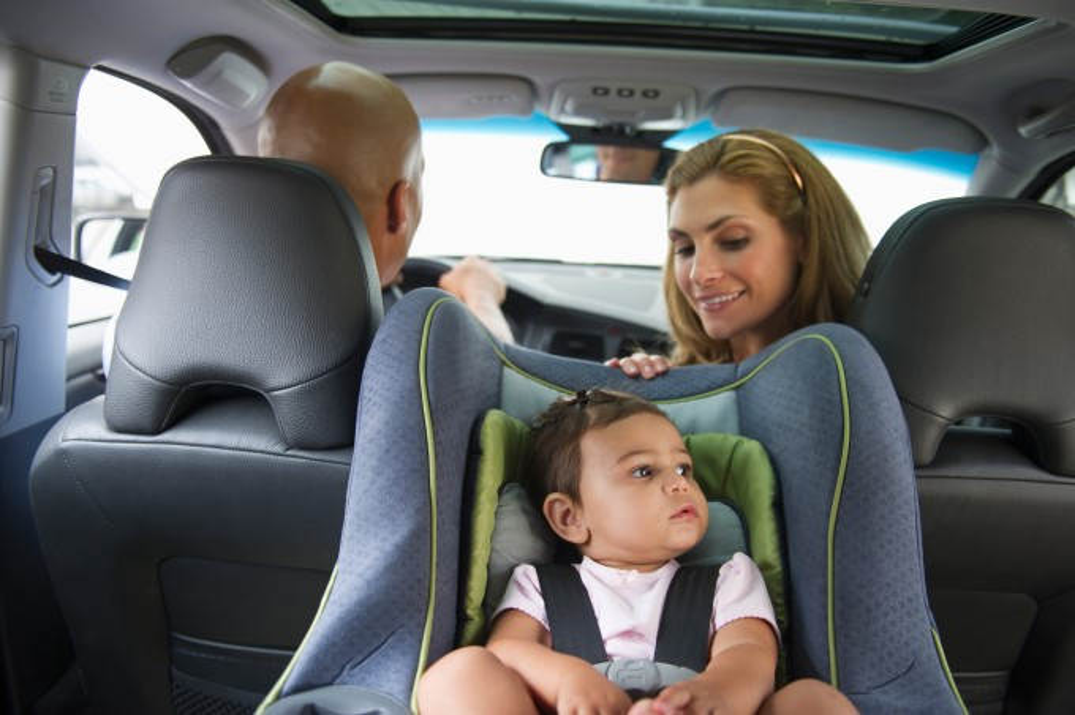 Família com filho em bebê-conforto cadeirinha de carro