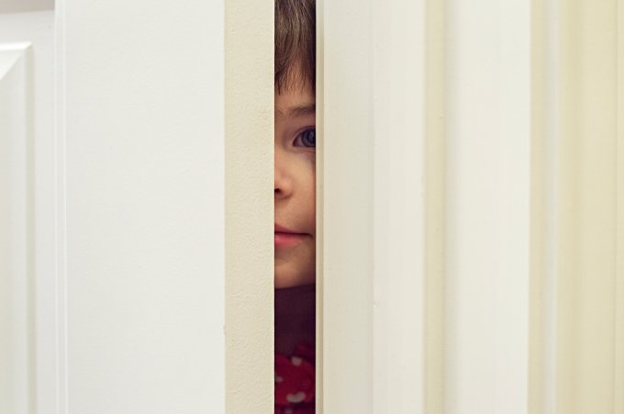 menina olhando atrás da porta