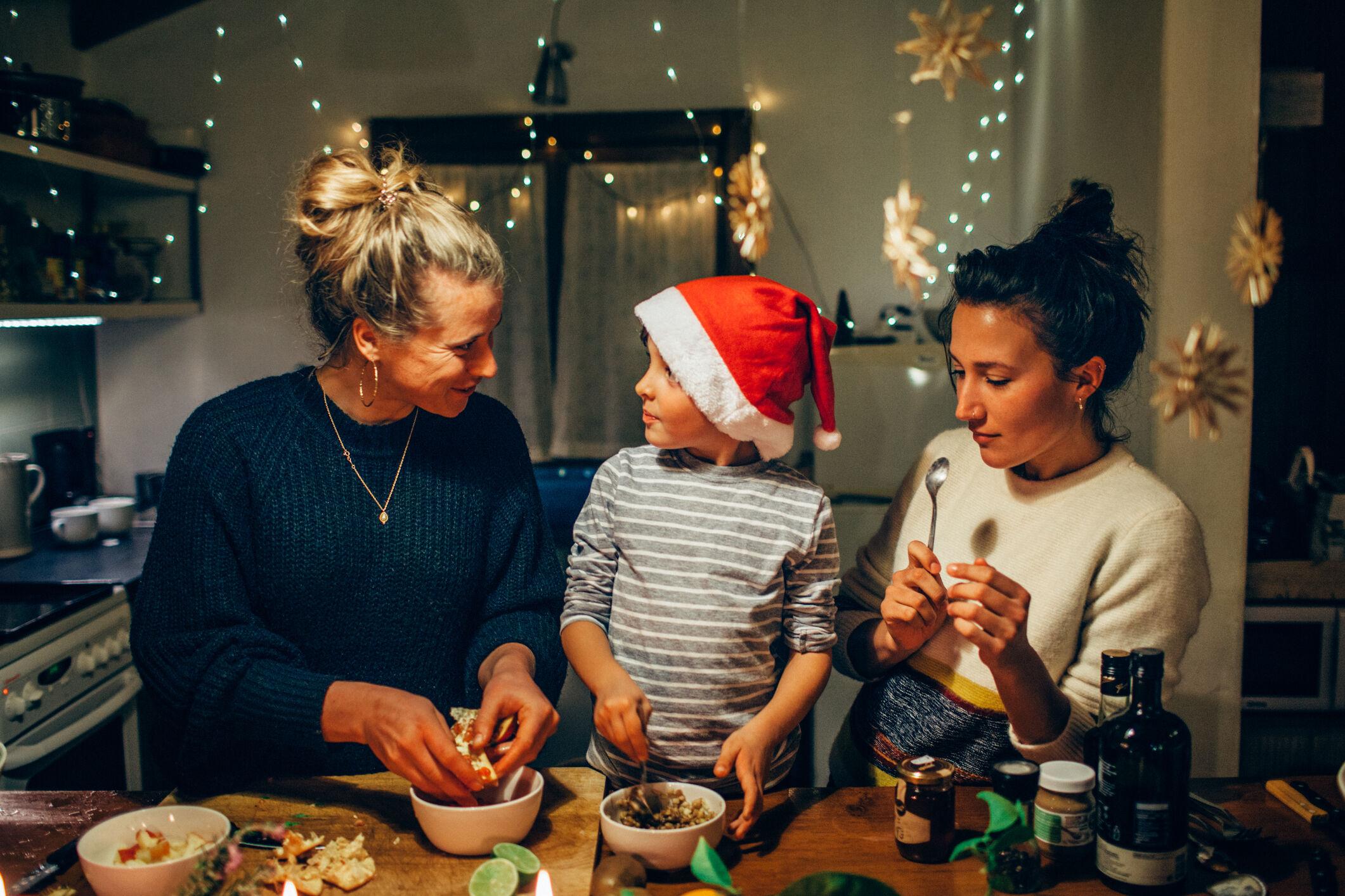 Duas mulheres preparando refeição de Natal com criança