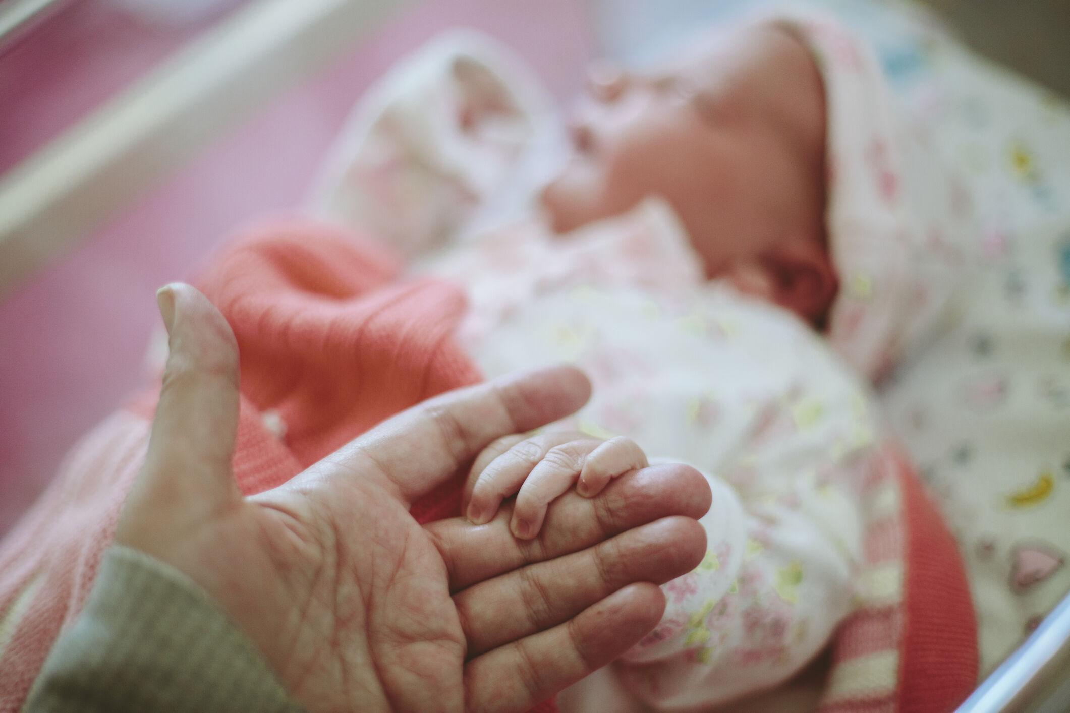 bebê recém-nascido e mãe segurando a mão