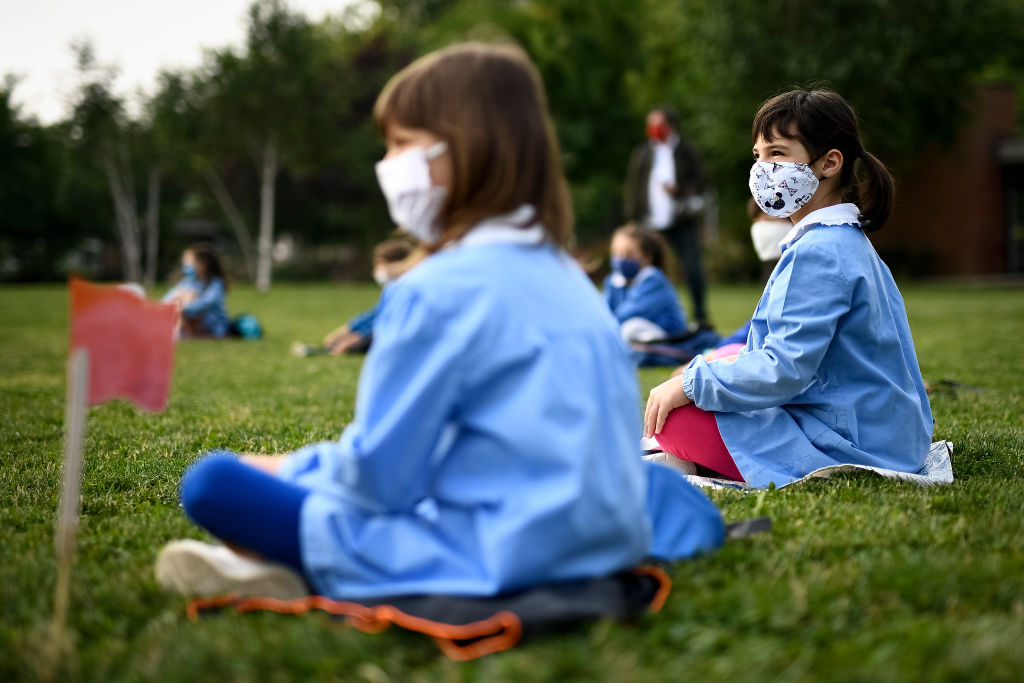 crianças sentadas na grama com máscara e distanciamento