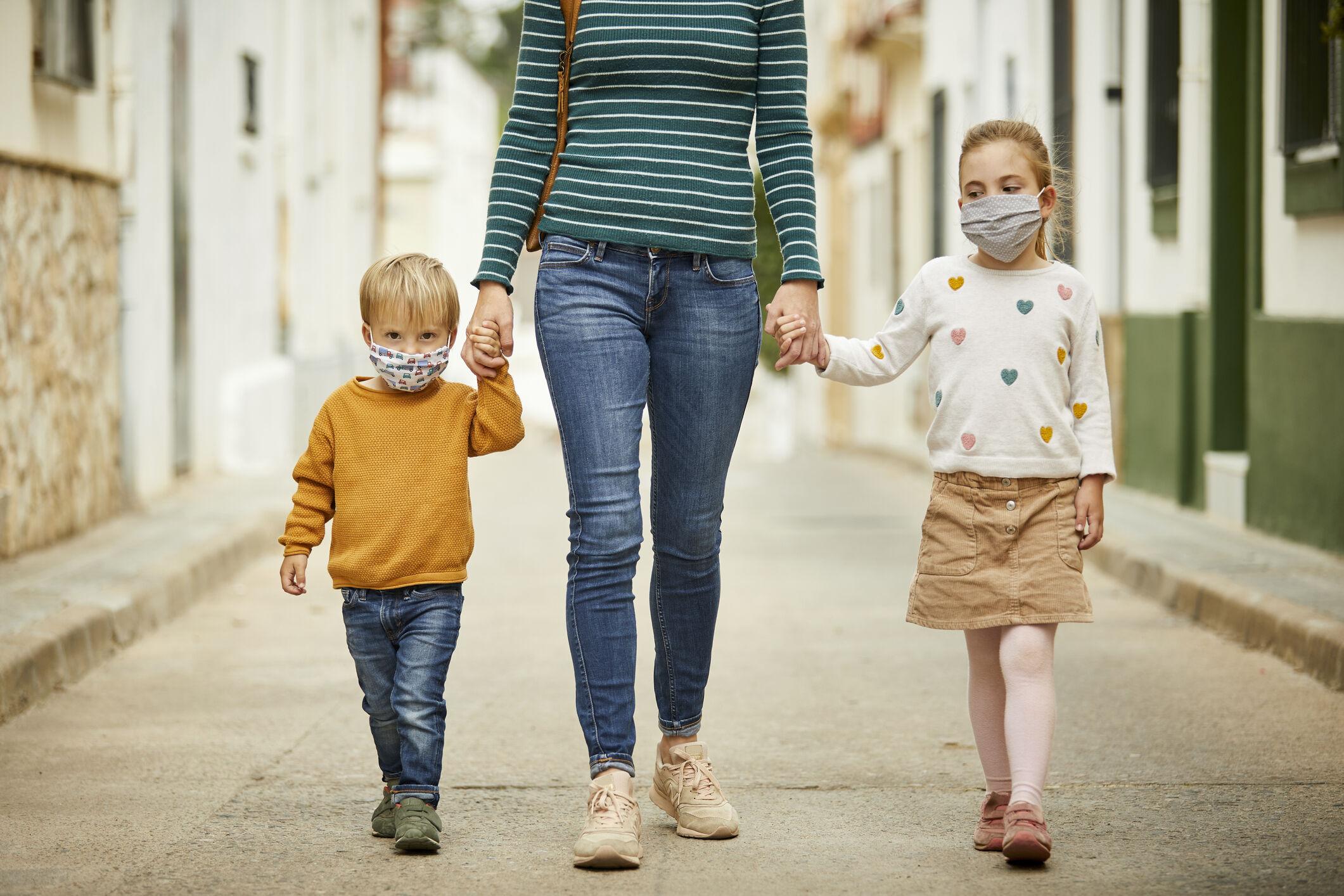Imagem de mulher andando de mãos dadas com duas crianças