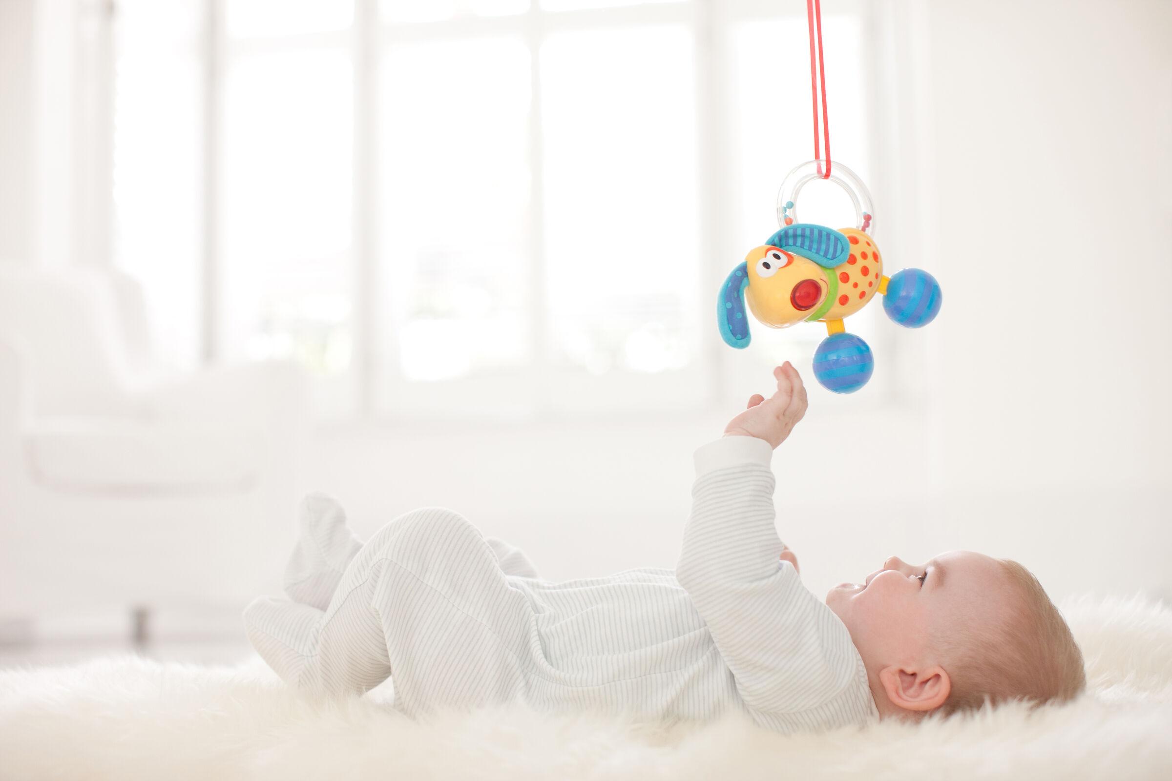 Bebê-deitado-no-berco-segurando-brinquedo-no-alto