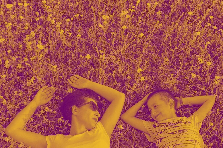 Mãe e filho deitados na grama