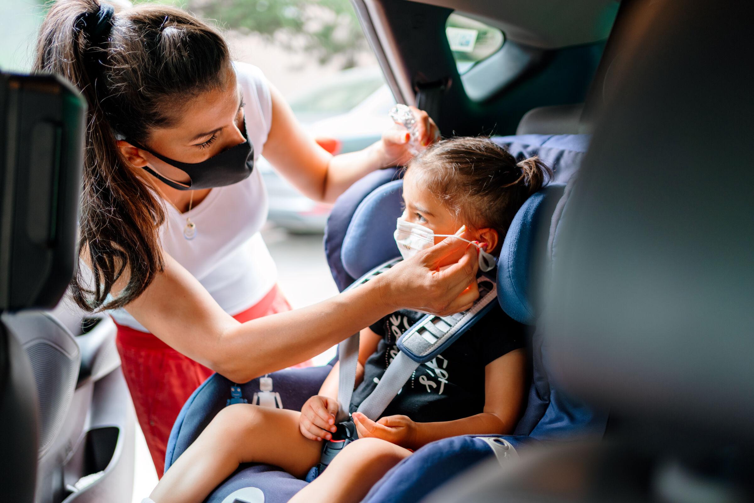 Mãe-colocando-mascara-na-filha-dentro-do-carro