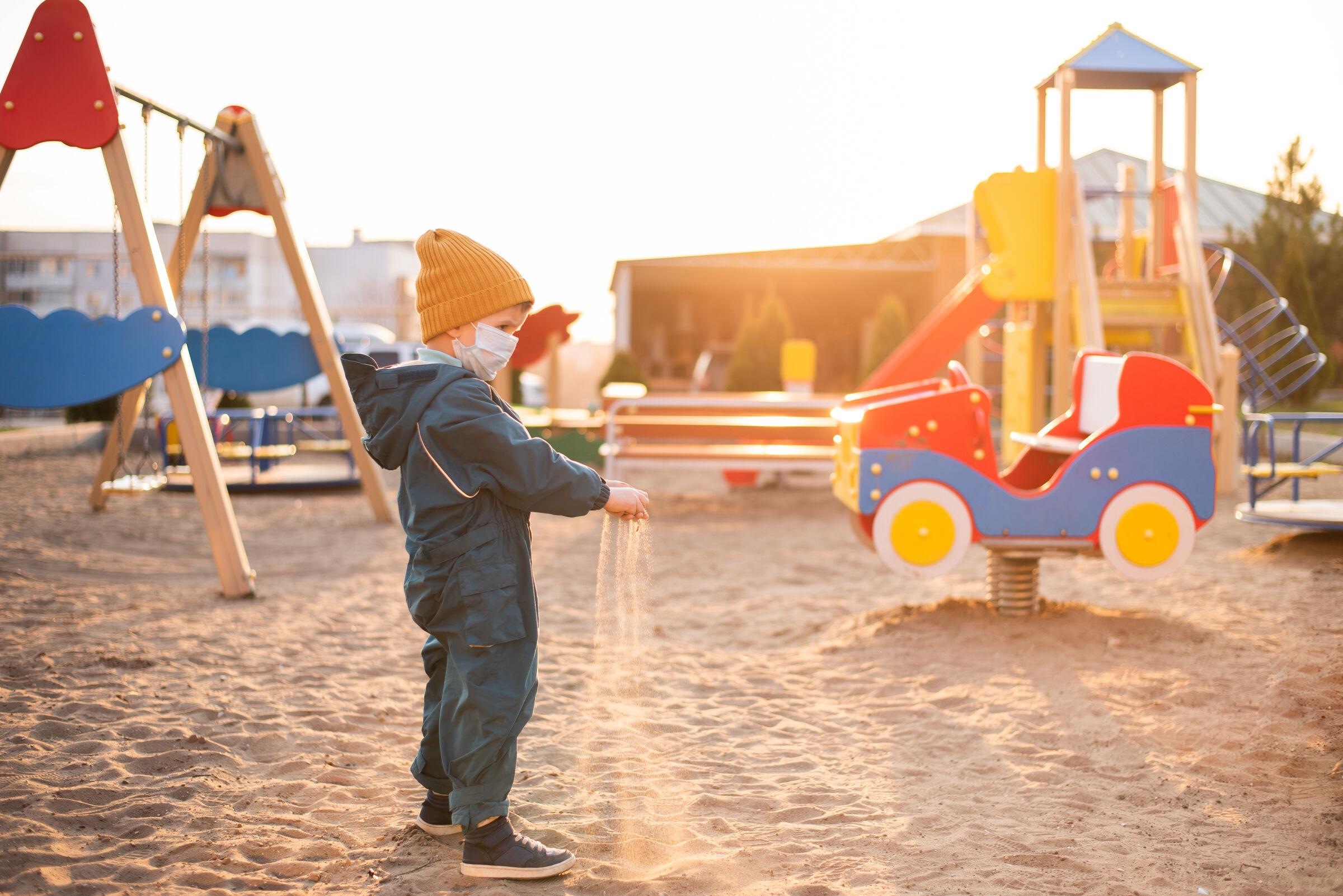 Menino-jogando-areia-no-chao-dentro-do-parquinho
