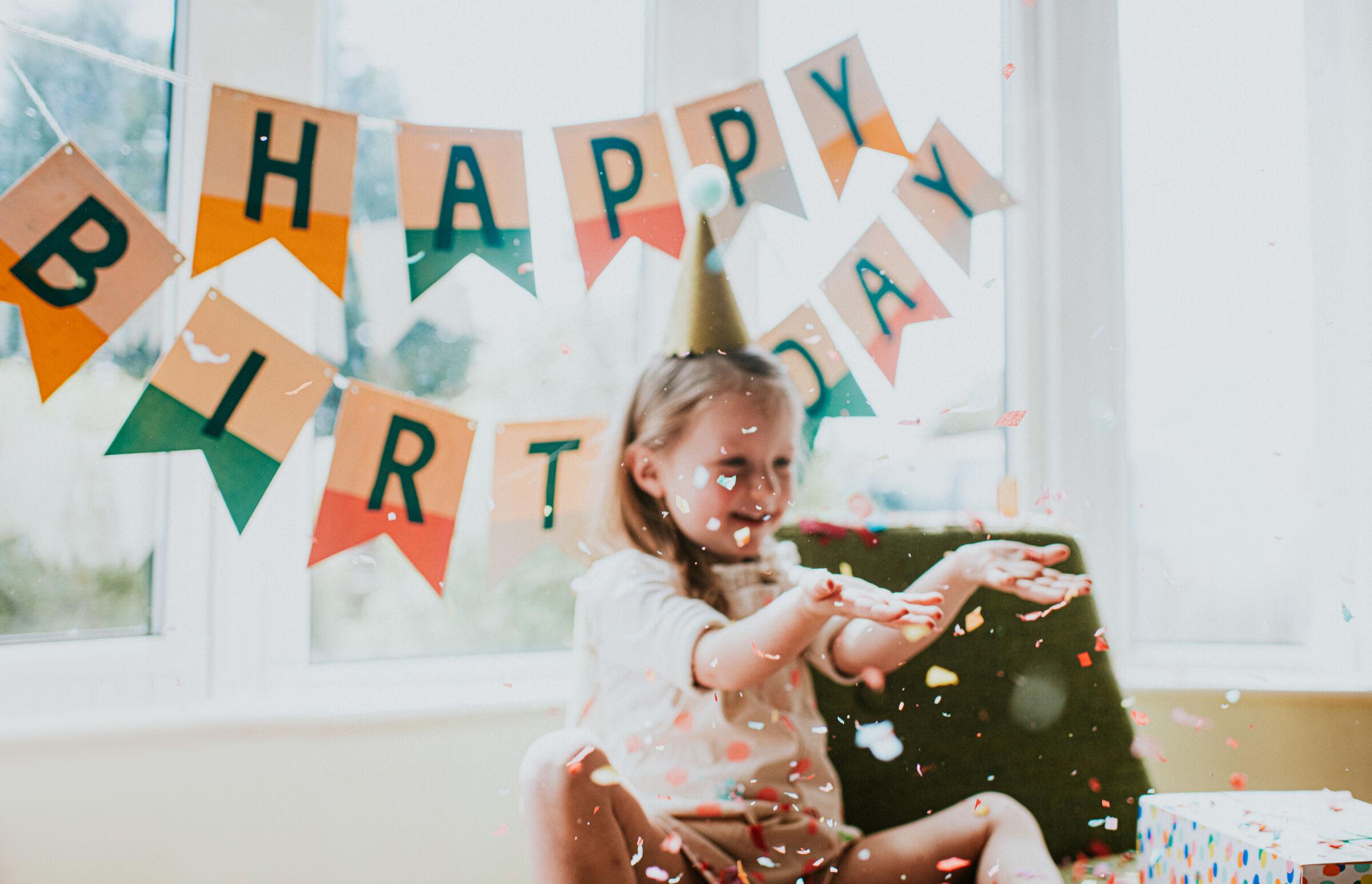 Crianca-jogando-confete-para-cima-no-seu-aniversario-em-casa